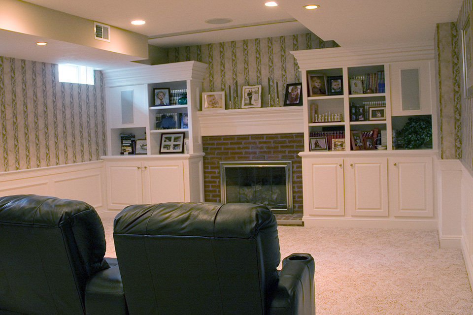 finshed basement with fireplace and custom built in cabinets